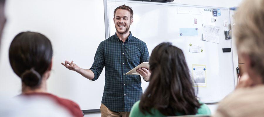 Uma imagem contendo um homem, três pessoas, um quadro branco ao fundo para aula de inglês para iniciantes